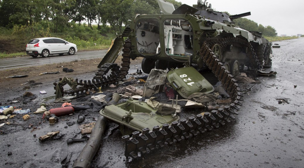 "A car travels past a destroyed pro-Russian APC near the city of Slovyansk, Donetsk Region, eastern Ukraine Monday, July 7, 2014. Ukraine's president Petro Poroshenko has called the capture of the Pro-Russian separatist stronghold of Slovyansk a ""turning point"" in the fight for control of the country's east. (AP Photo/Dmitry Lovetsky)"